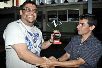 Jimmy Sánchez, Campeón Costarricense de Scrabble 2012, recibe de Rodrigo Grandos, presidente de Escrablística, su trofeo de primer lugar.
